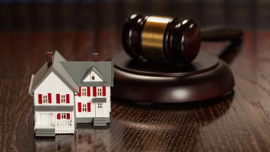 Gavel and Small Model House on Wooden Table With Law Books In Background.