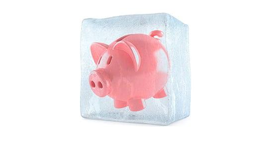 Piggybank with ice cube isolated on white background