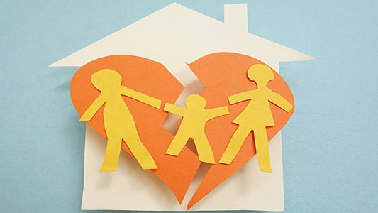 Paper family over torn heart, on house – divorce concept